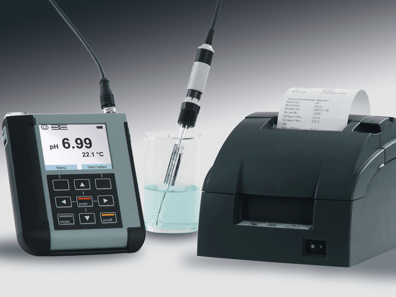portable measuring device portavo connected via cable to a sensor in a glass beaker with clear liquid. next to it a small black printer with a print-out coming out of the top