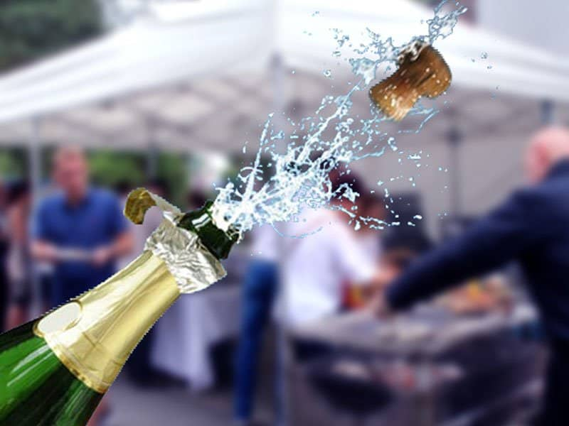 cork popping out of champagne bottle with party going on in a tent in the background