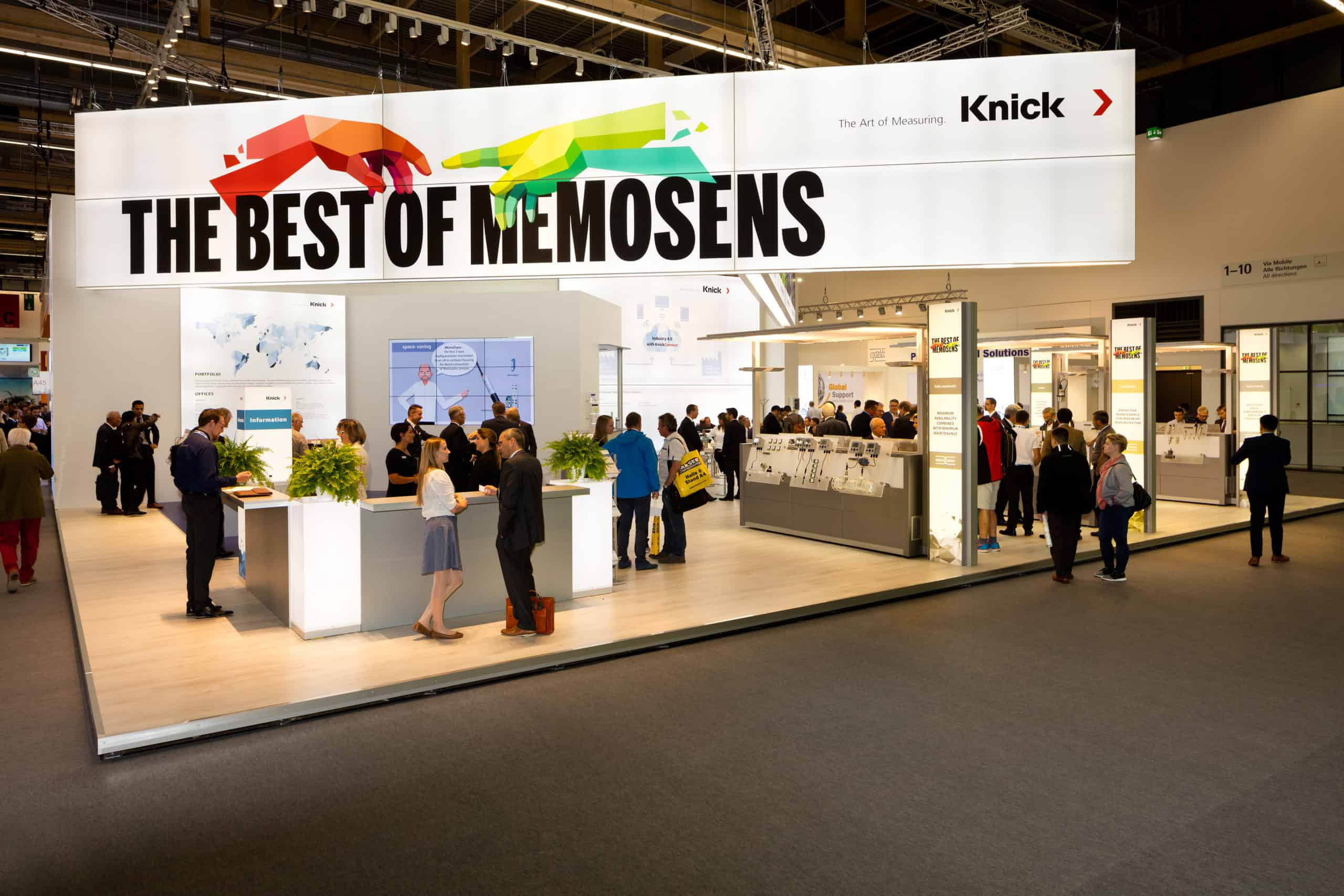 Knick exhibition stand including several white display areas and lots of people milling around with a large sign above reading the best of memosens